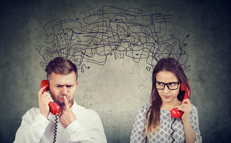 Confused couple woman and man talking on the phone exchanging with many negative thoughts royalty free stock image