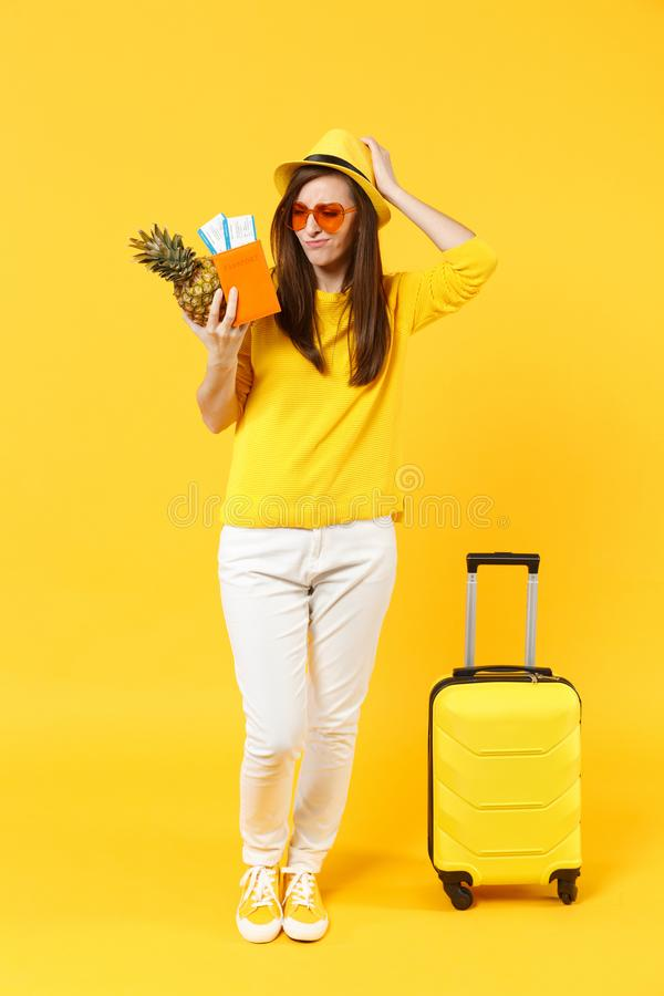 Preoccupied traveler tourist woman in hat hold passport tickets, fresh pineapple fruit isolated on yellow orange. Background. Passenger traveling abroad on royalty free stock photo