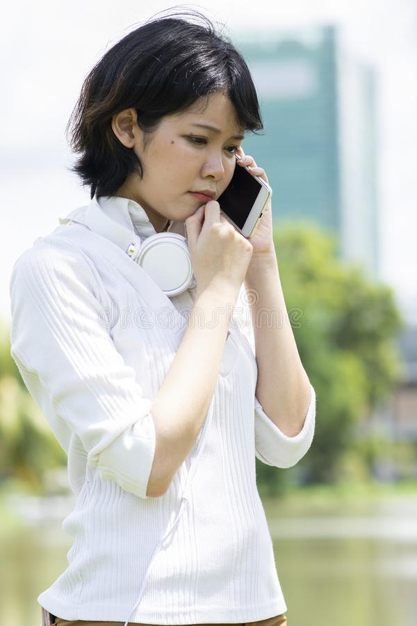 Preocupación de la mujer asiática que hace llamada de teléfono en jardín fotos de archivo libres de regalías