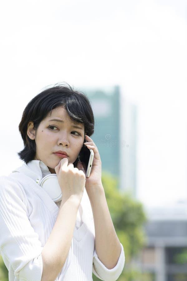 Preocupaci?n de la mujer asi?tica que hace llamada de tel?fono en jard?n imágenes de archivo libres de regalías