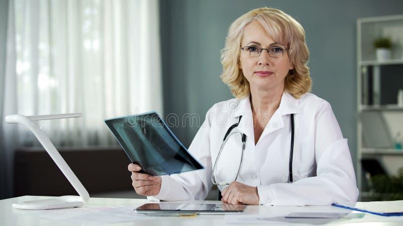 Preocupado del doctor de la salud del paciente que mira seriamente en cámara, medicina imagen de archivo libre de regalías