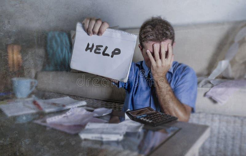 Preocupante joven en el hombre de la tensión en casa que calcula costos del impuesto del mes con los pagos de la contabilidad de  imágenes de archivo libres de regalías
