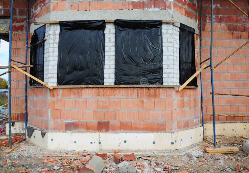 Prepárese para proteger la casa inacabada Windows para que el invierno evite nieve y la lluvia dentro fotografía de archivo libre de regalías