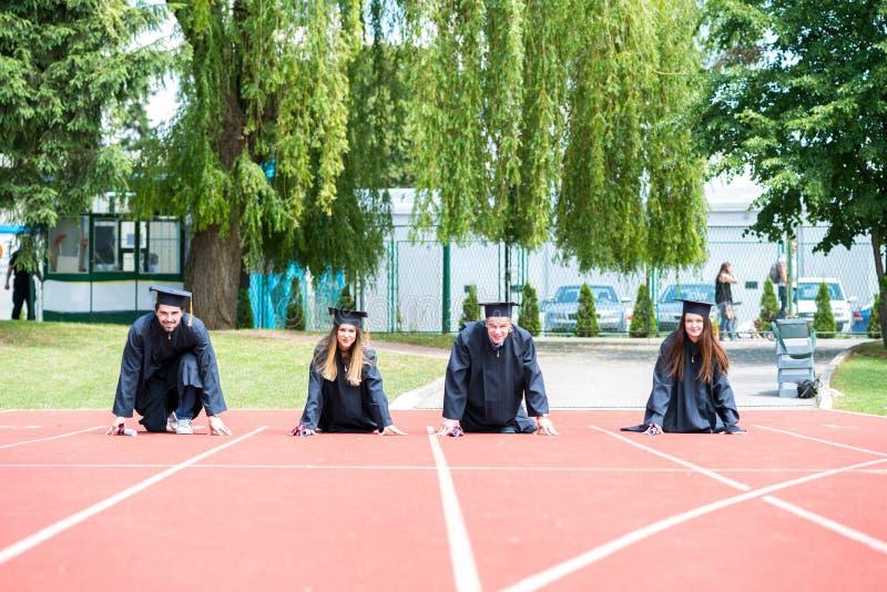 Prep graduatiegroep studenten die op atletisch spoor vieren, stock foto