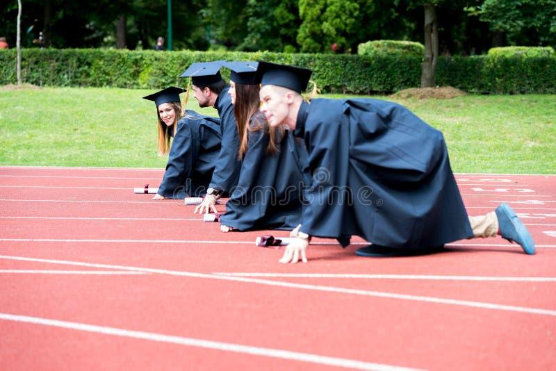 Prep graduatiegroep studenten die op atletisch spoor vieren, stock foto's