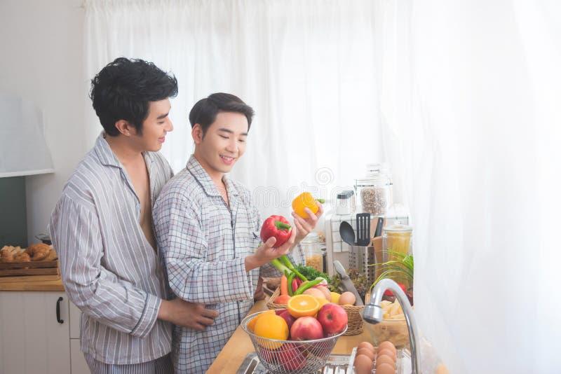 Prepairing frukost för homosexuella par i kök royaltyfri foto
