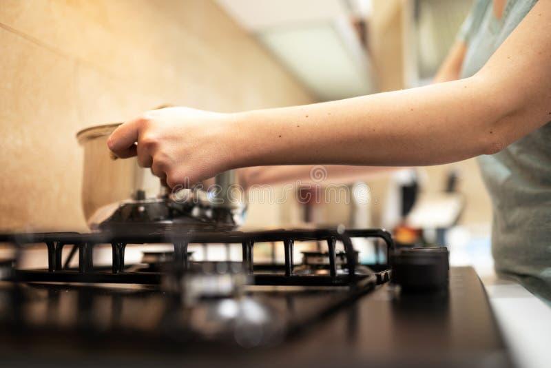 Prepairing matställe för härlig hemmafru för ung kvinna, håll i den stora stålkastrullen för händer som står den på gas-ugnen arkivbild