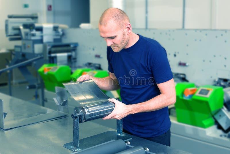 Preparação cortando giratória de Flexo O trabalhador em imprimir a fábrica, estando ao lado da preparação da máquina imprimindo c fotos de stock