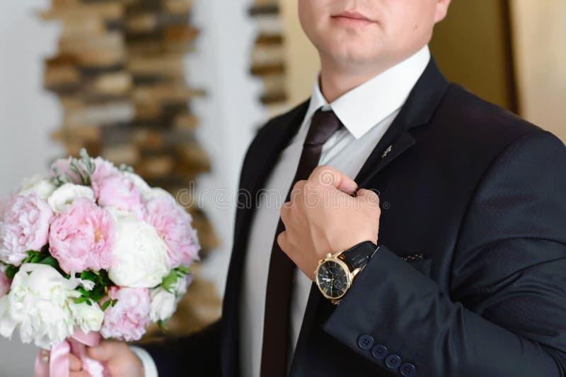 Preparação da manhã dos noivos, noivo considerável que obtém vestido e que prepara-se para o casamento, no terno cinzento em uma  imagens de stock royalty free