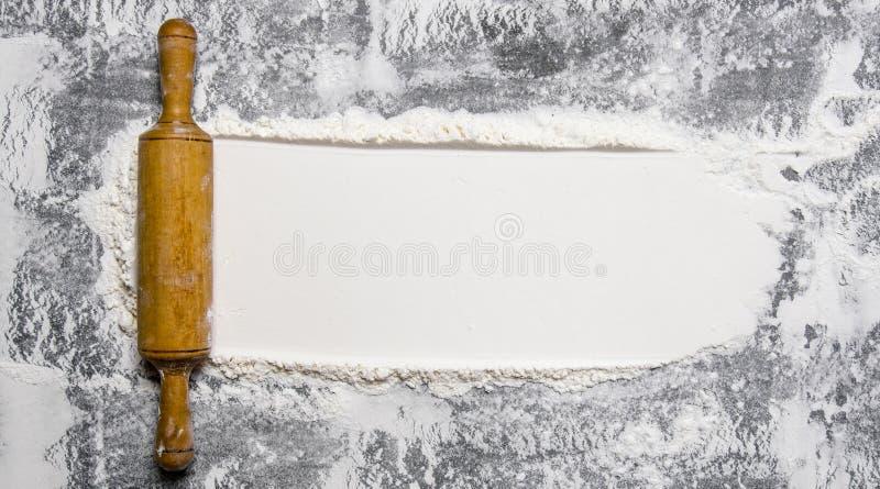 Preparação da massa O pino do rolo com farinha em um fundo de pedra imagem de stock