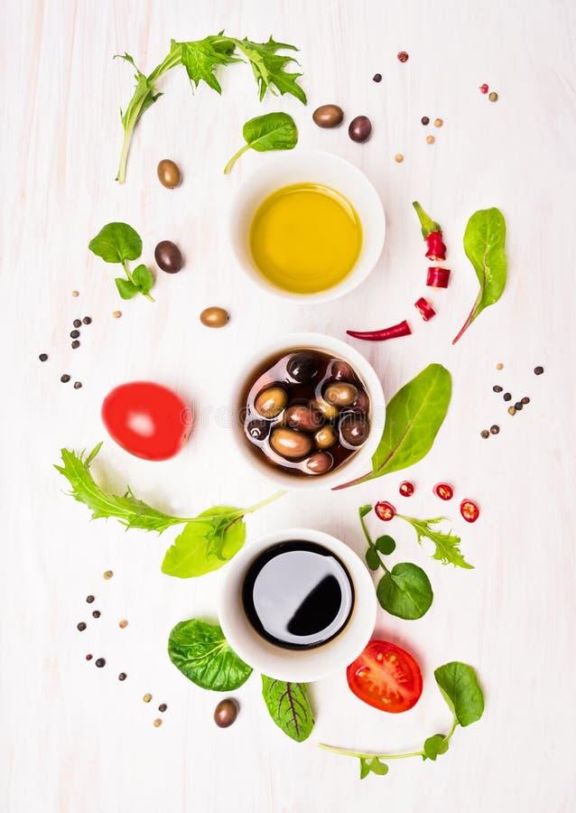 Preparação da salada com molhos, azeitonas, as folhas selvagens das ervas, o pimentão, o óleo e os tomates fotografia de stock royalty free