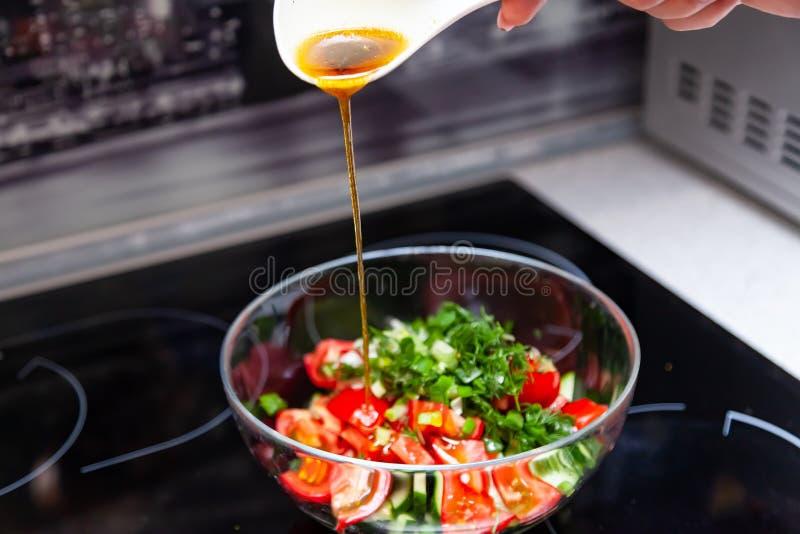 Preparação da salada dos legumes frescos, dos pepinos, dos tomates e dos verdes com uma colher plástica branca de que derrama um  foto de stock