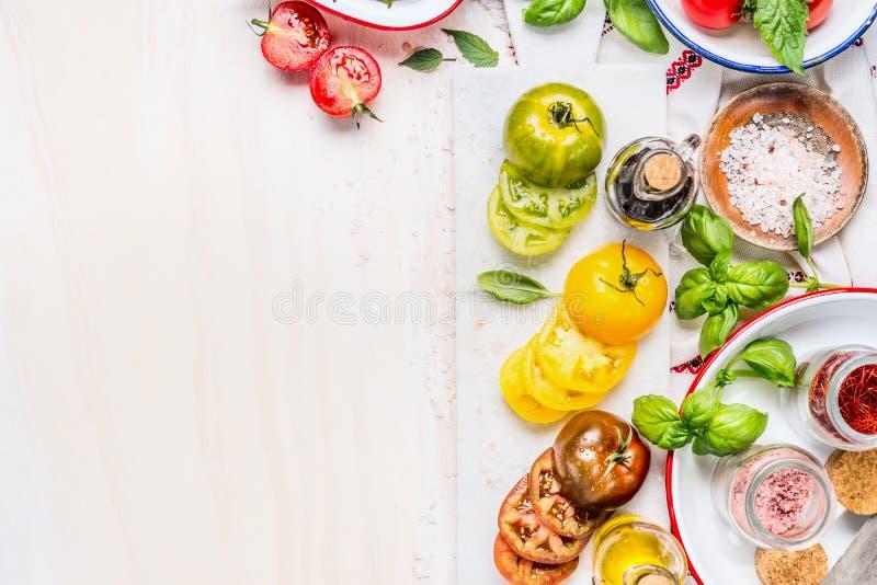 Preparação da salada dos tomates Tomates que cozinham ingredientes na placa de corte de mármore branca Vários tomates cortados co fotografia de stock royalty free