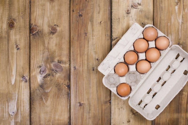 Preparação de bolos caseiros em um fundo de madeira Ingredientes e acessórios para a cozinha e em casa Ovos em uma caixa e imagem de stock royalty free