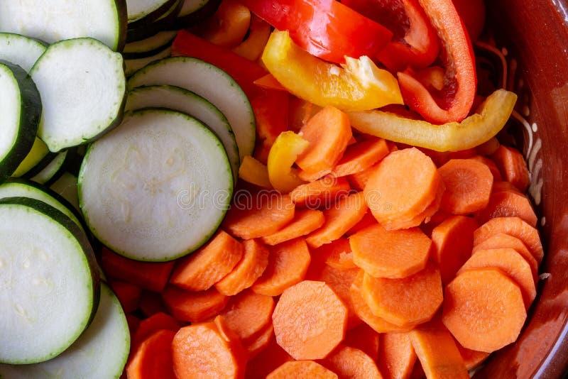 Preparação de cenouras coloridas dos vegetais, pimentas de sino, courgettes na placa de corte fotos de stock