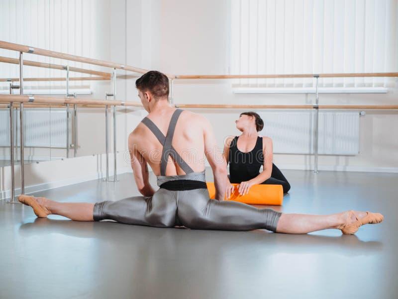 Preparação do corpo antes do desempenho no estúdio do bailado Dançarino masculino e bailarina que aquecem-se perto da barra no en imagem de stock royalty free