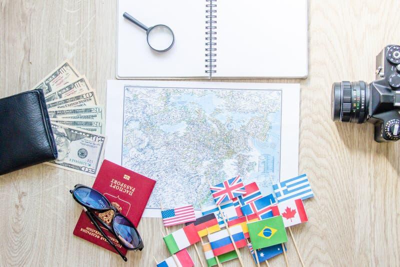 Preparação do curso: dinheiro, passaporte, mapa de estradas, óculos de sol, lupa, câmera retro do filme, caderno na tabela de mad fotografia de stock royalty free