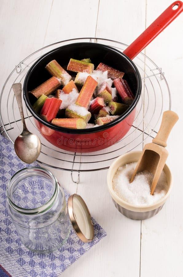Preparação do doce feito home do ruibarbo em um potenciômetro vermelho do esmalte fotografia de stock