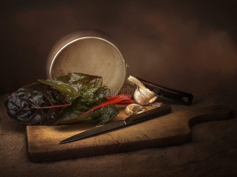 Preparação dos alimentos vegetal da acelga do rubi aka, ainda vida com alho Pintura da luz do estilo do claro-escuro Beta vulgar foto de stock