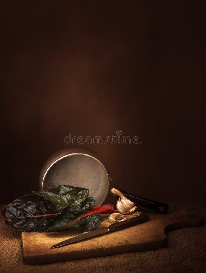 Preparação dos alimentos vegetal da acelga do rubi aka, ainda vida com alho Pintura da luz do estilo do claro-escuro Beta vulgar fotos de stock