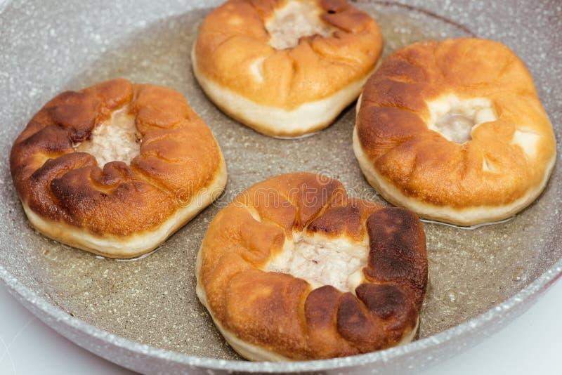 Preparação dos belyashes Belyashi tradicional das tortas de carne do russo em uma frigideira Culinária do russo, a Bashkir e a Ta imagem de stock