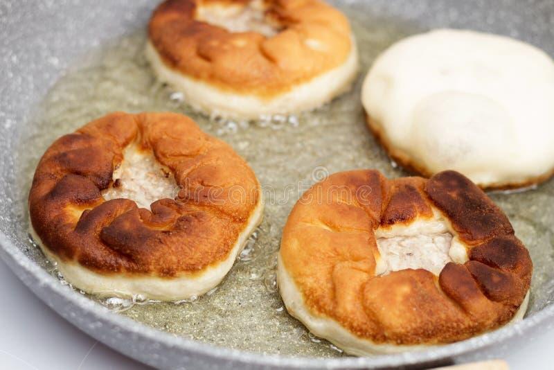 Preparação dos belyashes Belyashi tradicional das tortas de carne do russo em uma frigideira Culinária do russo, a Bashkir e a Ta foto de stock royalty free
