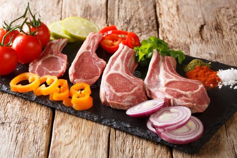 Preparação para grelhar costeletas de cordeiro cruas com legumes frescos e close-up das especiarias em uma placa da ardósia horiz foto de stock royalty free