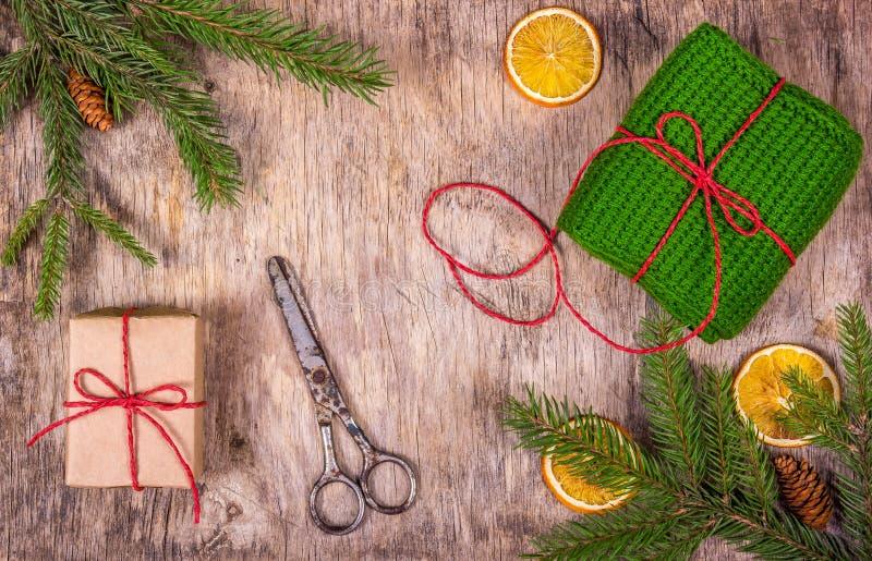 Preparação para o Natal Embalagem dos presentes Os ramos Spruce, laranja, fizeram malha o presente e as facas Presente do ` s da  imagem de stock royalty free
