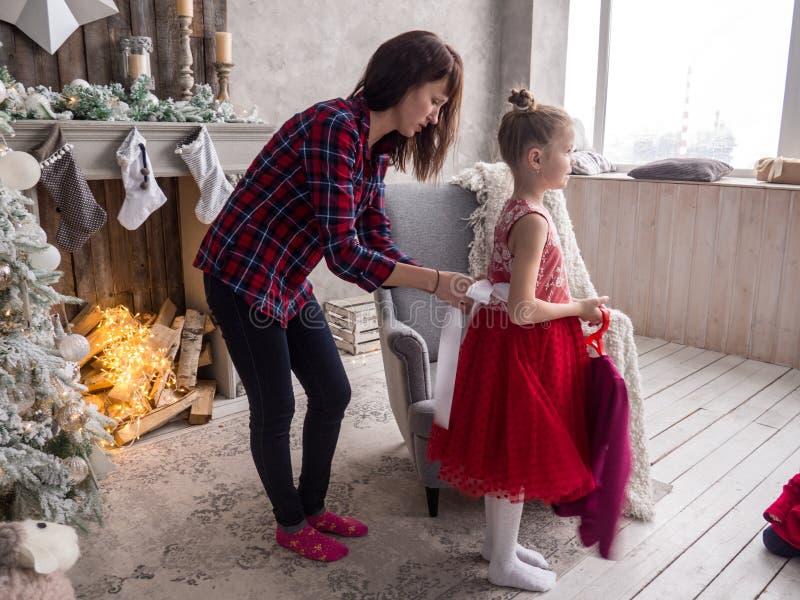 Preparação para o Natal: A mamã ajuda sua filha posta sobre um vestido vermelho para a bola do Natal foto de stock