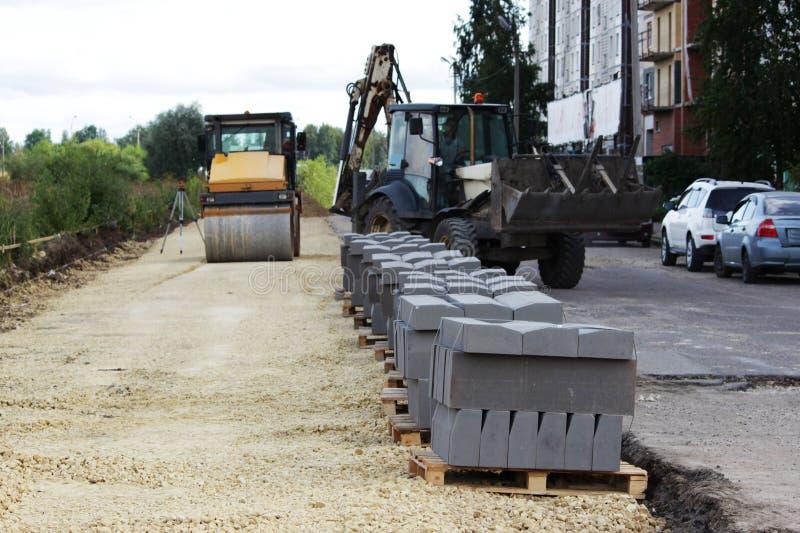 preparação para o reparo do local antes de colocar de pavimentos O rolo comprime a superfície, o carregador descarrega imagens de stock royalty free