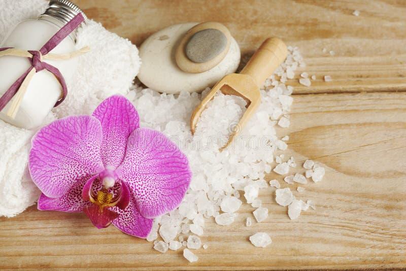 A preparação para tratamentos dos termas, o sal, as toalhas, a loção e uma orquídea brilhante florescem em uma tabela de madeira fotografia de stock