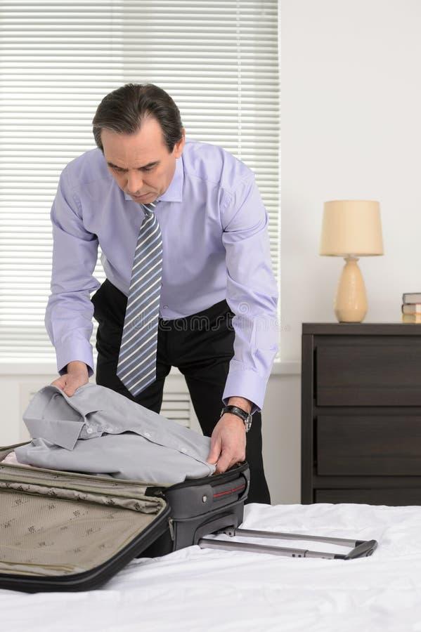 Preparação para uma viagem de negócios. Homem de negócios maduro que embala seu cl