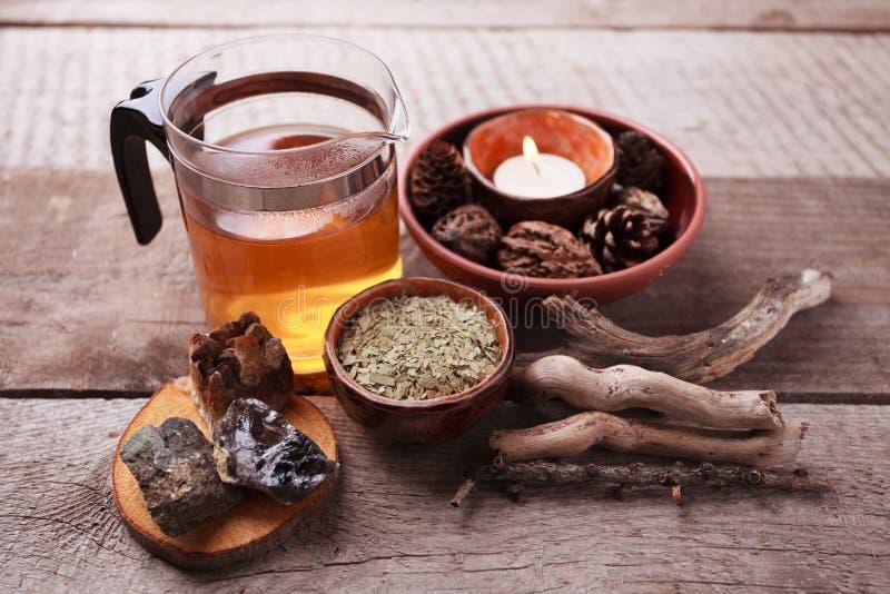 Preparação saudável da tisana com o bule asiático de vidro, vela detalhes de madeira e de pedra e fundo de madeira rústico do vin fotografia de stock
