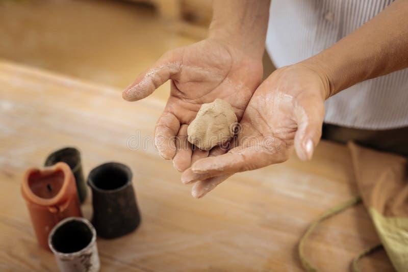 Preparações da terra arrendada de Handicraftsman para o vaso futuro em suas mãos imagens de stock