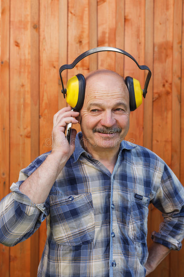 Preparações para obras em sua casa de campo do verão O construtor consulta pelo telefone com o chefe foto de stock