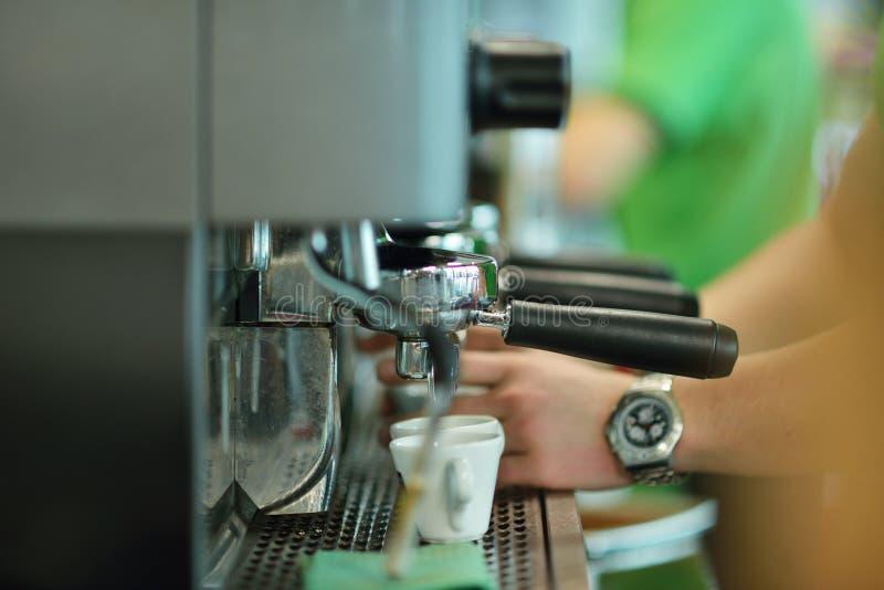 Prepara el café express en su cafetería, primer foto de archivo