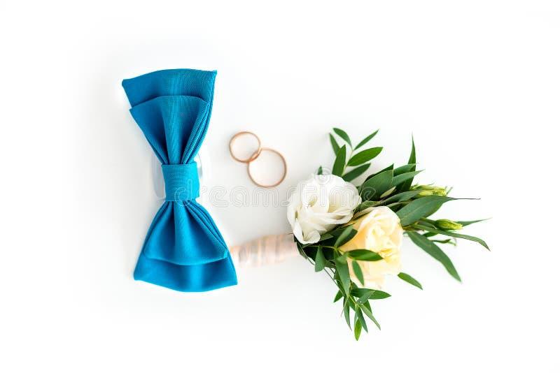 Prepara los accesorios Corbata de lazo azul, casandose los anillos y boutonniere de oro de la flor en fondo blanco aislado fotos de archivo libres de regalías