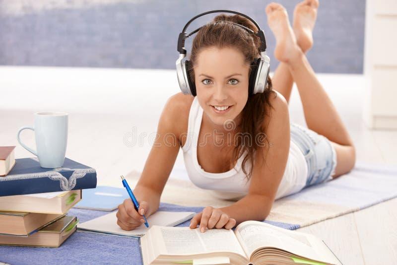 Preparación bonita de la escritura de la muchacha que pone en suelo imagen de archivo libre de regalías