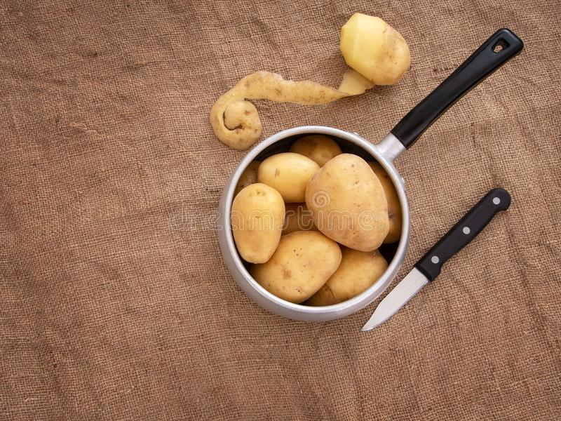 Preparación de comida, pelando las patatas en rústico todavía fijando vida con el cazo, cuchillo, yute de la arpillera aka Visión fotos de archivo