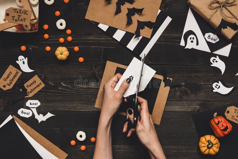 Preparación de Halloween Manos que hacen las tarjetas y la decoración de Halloween usando el papel del arte foto de archivo