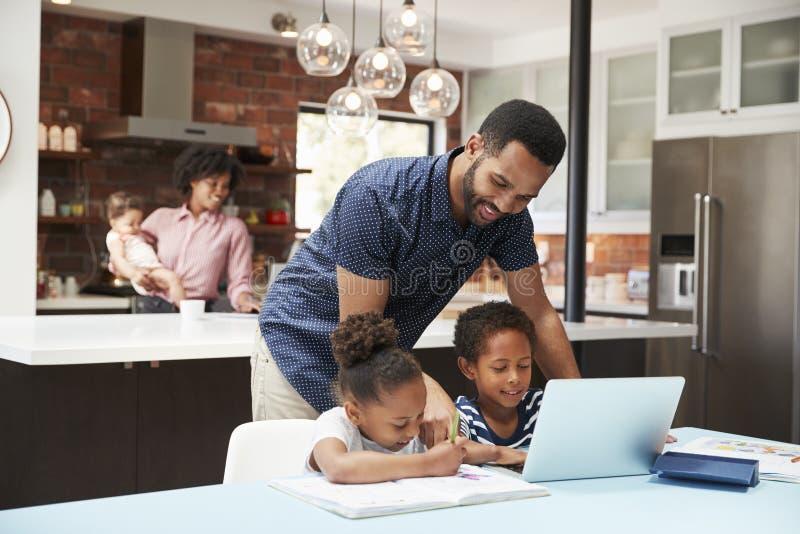 Preparación de Helps Children With del padre mientras que la madre con el bebé utiliza el ordenador portátil en cocina fotos de archivo