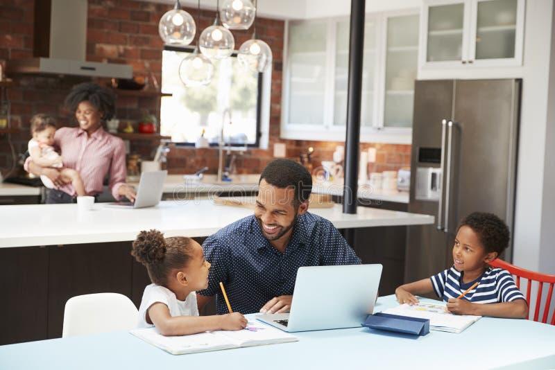 Preparación de Helps Children With del padre mientras que la madre con el bebé utiliza el ordenador portátil en cocina fotografía de archivo