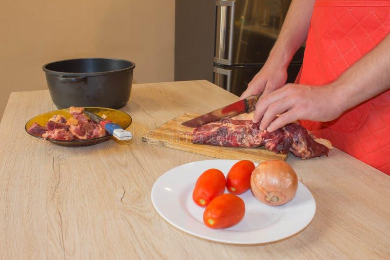 Preparación de la comida, de la carne y de verduras manos del cocinero que cortan la carne cruda fotos de archivo libres de regalías