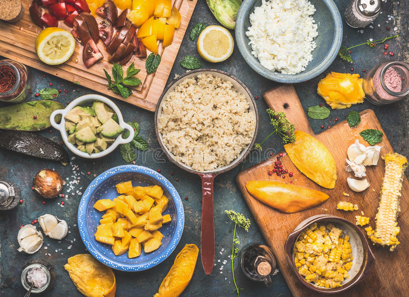 Preparación de la ensalada de la quinoa con las verduras y las frutas que cocinan los ingredientes en el fondo rústico oscuro, vi fotografía de archivo libre de regalías