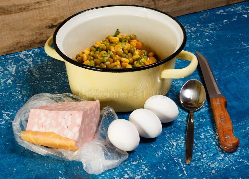Preparación de la ensalada del maíz y de guisantes conservados con los huevos, cebollas imagen de archivo
