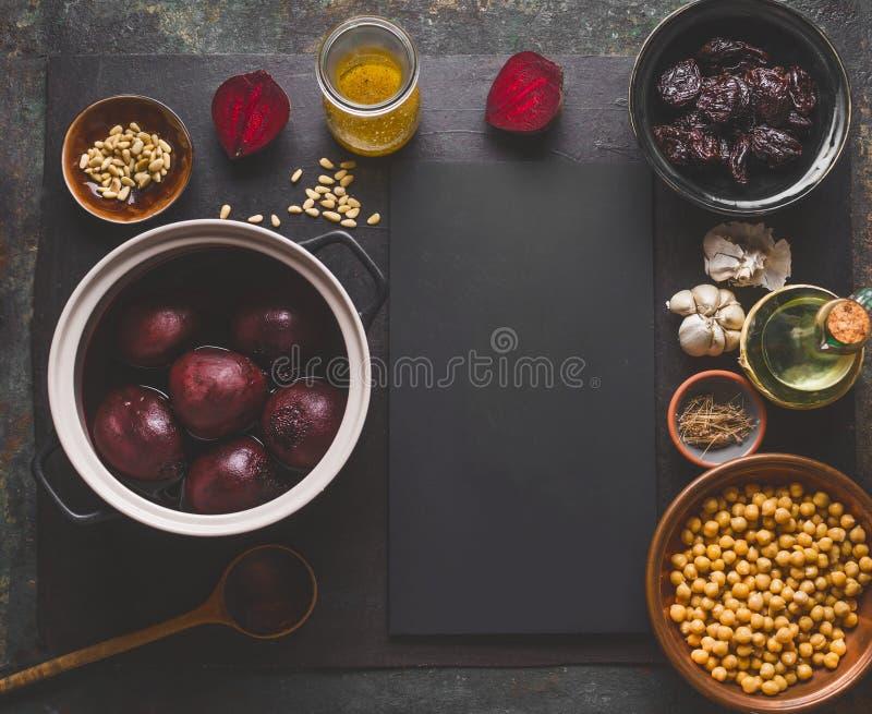Preparación de la ensalada de la raíz de la remolacha con las nueces de pino, los garbanzos y las pasas en el fondo oscuro, visió fotografía de archivo