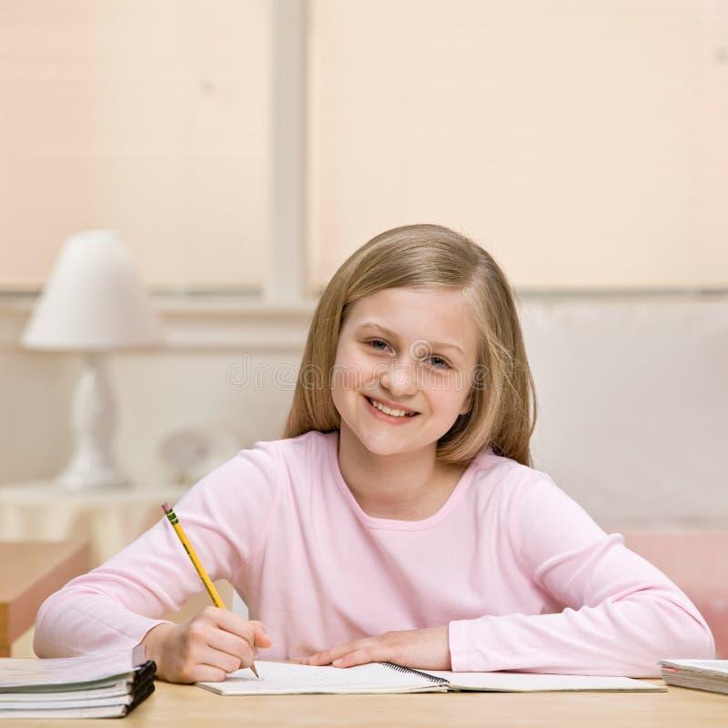 Preparación de la escritura de la chica joven en cuaderno imagen de archivo