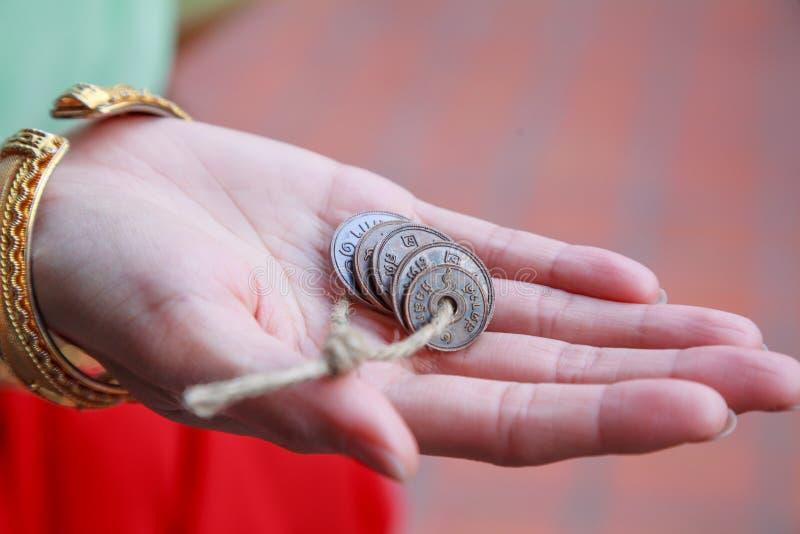 Preparación de la mujer en el estilo retro del vintage que da monedas monetarias tailandesas antiguas viejas del metal bajo Comer imágenes de archivo libres de regalías