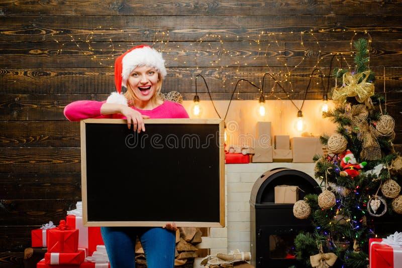 Preparación de la Navidad Mujer de la Navidad que sostiene un escritorio negro para el texto Espacio negro de la copia del tabler fotografía de archivo libre de regalías