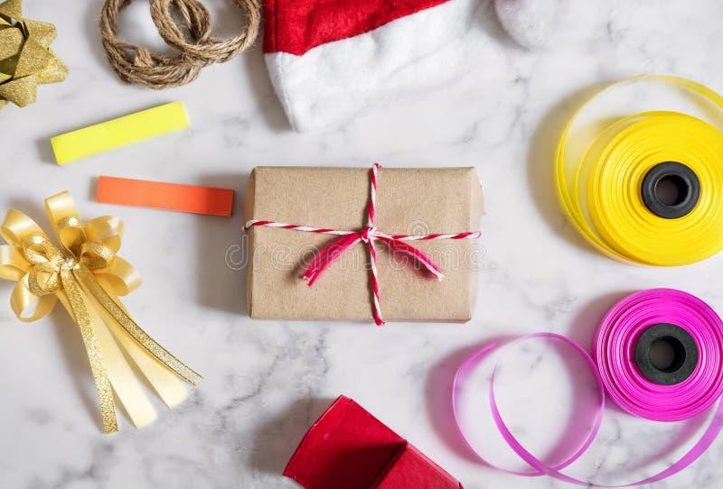 Preparación de los regalos de la Navidad en la piedra de mármol blanca Caja de regalo con el sombrero rojo de santa, caja de rega imágenes de archivo libres de regalías